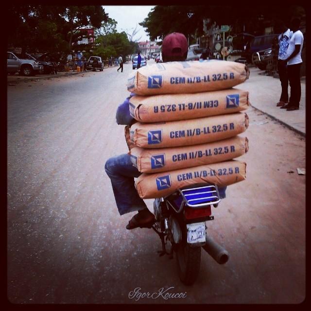 un Zém transporte 5 paquets de 50kg de ciments derrière sa moto et deux devant. #Cotonou #Bénin